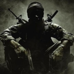 Backlit Call of Duty soldier sitting cross-legged with one weapon, a handgun, at the ready with a rifle strapped to his back.