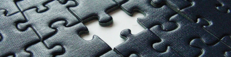 black puzzle pieces fit together with one piece missing revealing a stark white gap in the puzzle pieces.